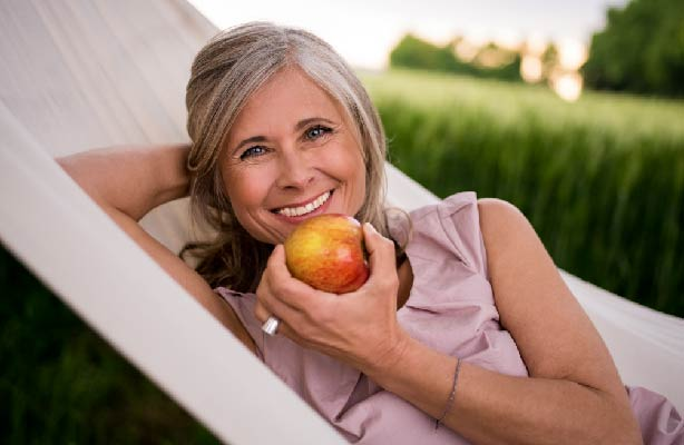 older woman eating apple outside