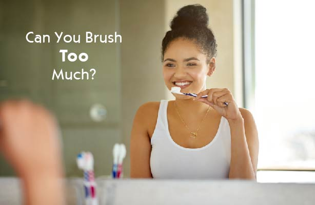 young woman in front of mirror brushing teeth