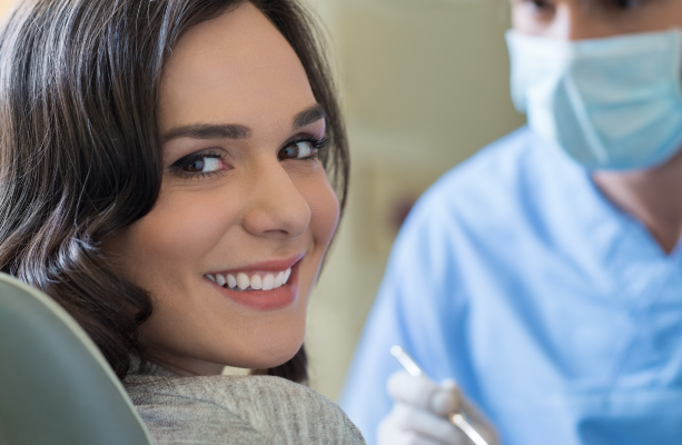 woman in dental chair smiling with dentist behind her