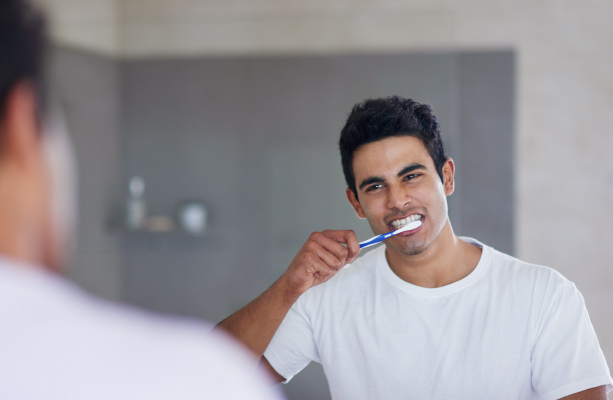 dark haired man standing in front of mirror brushing teeth with fluoride toothpaste to help teeth