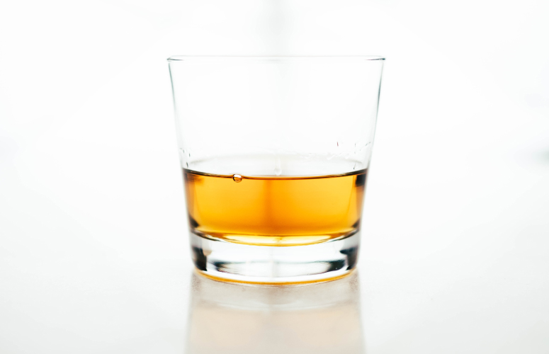 Clear glass of yellow-orange alcohol that will dissolve your teeth's enamel over time