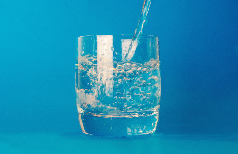 Clear glass against a sky blue background having water poured into it as a healthy alternative to alcohol-based mouthwash