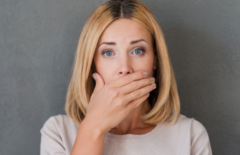 woman covering her mouth with her hand to hide gum recession
