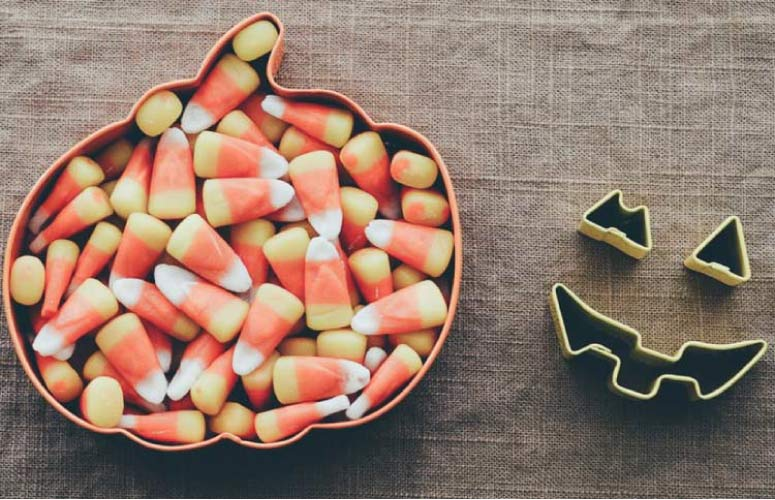 pumpkin shaped bowl full of candycorn