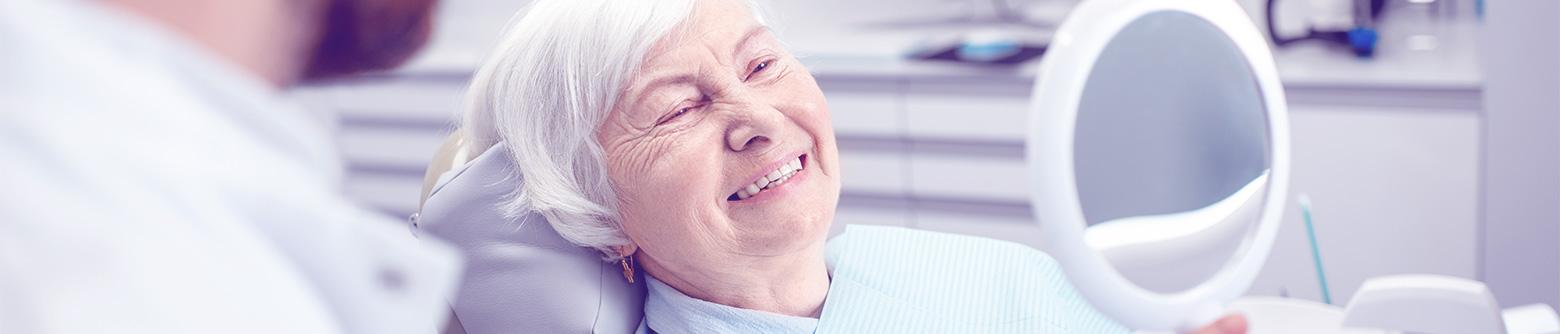 Elderly woman looking at smile in mirror