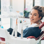 Brunette woman in a dental chair smiles before receiving root canal treatment in Canton, GA