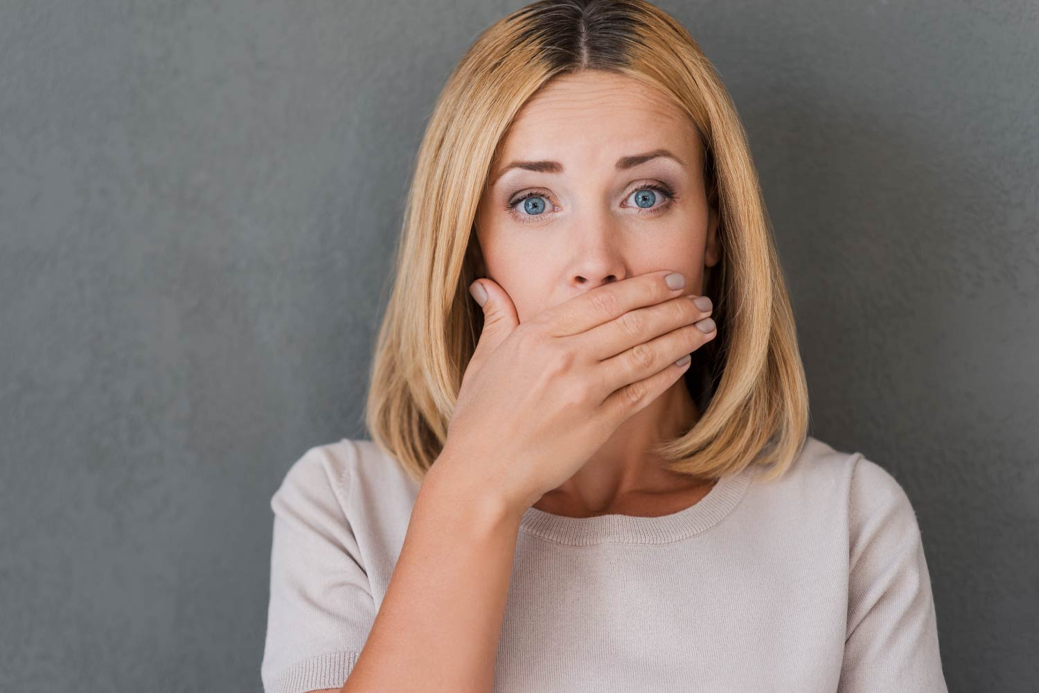 Blonde woman with brown roots covers her mouth in embarrassment because she has bad breath