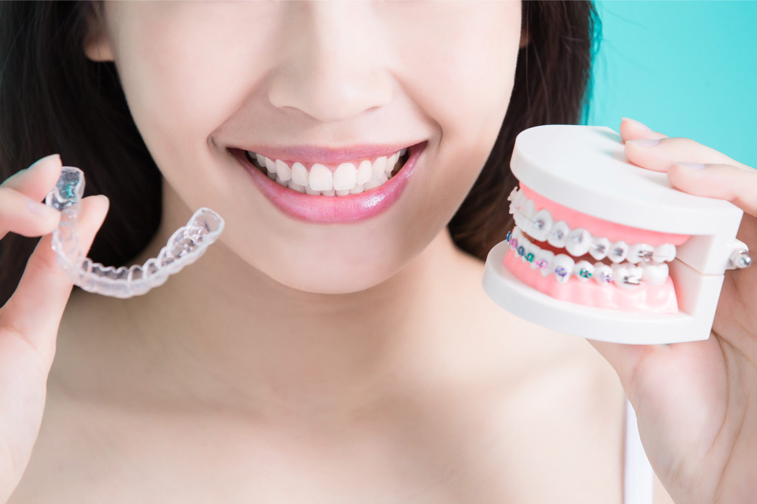 Woman holds Invisalign aligners and braces to compare the two orthodontic treatments