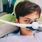 Young boy in the dental chair with a mask dispensing nitrous oxide dental sedation.