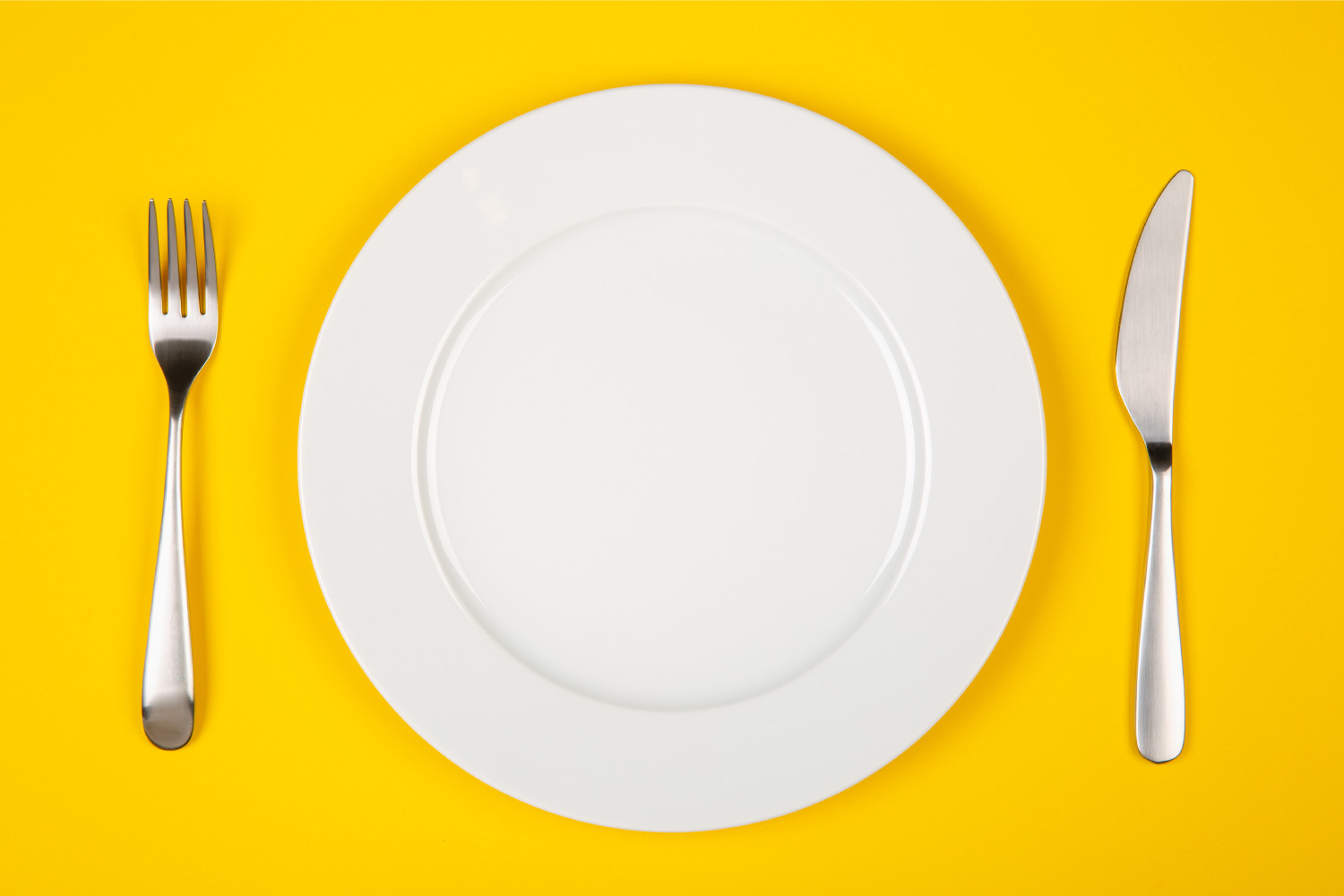 Aerial view of a white plate, fork, and knife on a yellow table for food
